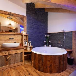 Modelo de cuarto de baño principal, rústico, con puertas de armario de madera en tonos medios, jacuzzi, encimera de madera, paredes blancas, suelo de madera en tonos medios, lavabo sobreencimera, suelo marrón y encimeras marrones