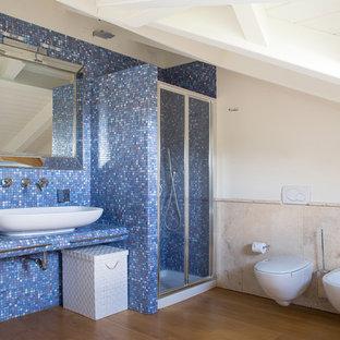Immagine di una piccola stanza da bagno con doccia minimal con doccia ad angolo, bidè, piastrelle in gres porcellanato, pareti blu, parquet scuro, lavabo a bacinella, pavimento marrone e porta doccia scorrevole