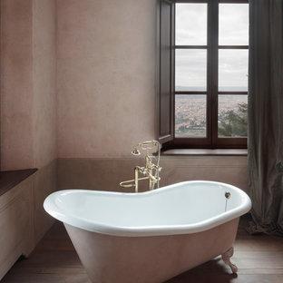 Immagine di una stanza da bagno classica di medie dimensioni con vasca con piedi a zampa di leone, pareti rosa, pavimento in legno massello medio e pavimento marrone