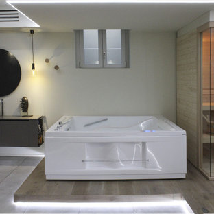 Inspiration for a modern light wood floor, single-sink and tray ceiling bathroom remodel in Other with flat-panel cabinets, brown cabinets, a hot tub, a wall-mount toilet, beige walls, a vessel sink, laminate countertops, brown countertops and a floating vanity