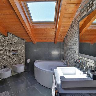 Réalisation d'une salle de bain principale minimaliste avec un bain bouillonnant, un WC suspendu, un mur gris et une grande vasque.