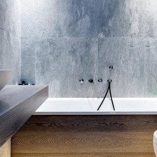 Modelo de cuarto de baño principal, contemporáneo, pequeño, con puertas de armario de madera clara, bañera encastrada, sanitario de pared, baldosas y/o azulejos grises, losas de piedra, paredes grises, suelo de madera pintada, lavabo sobreencimera, encimera de madera y suelo beige