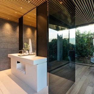 Ispirazione per una stanza da bagno moderna con ante bianche, piastrelle grigie, pavimento in legno massello medio, lavabo a consolle e pavimento marrone