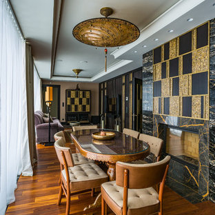 Стильный дизайн: гостиная-столовая в классическом стиле с коричневыми стенами, паркетным полом среднего тона, стандартным камином и коричневым полом - последний тренд
