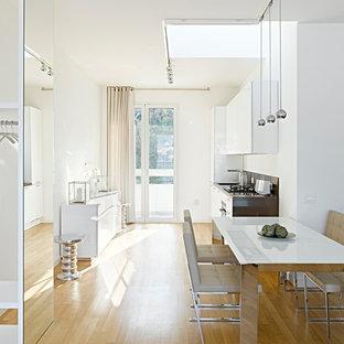 Idee per una grande sala da pranzo aperta verso la cucina minimal con pareti bianche e parquet chiaro