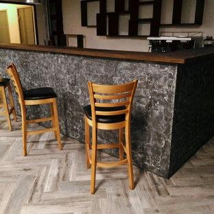 Foto de comedor urbano, grande, cerrado, con paredes grises, suelo laminado, chimenea lineal, marco de chimenea de hormigón y suelo gris