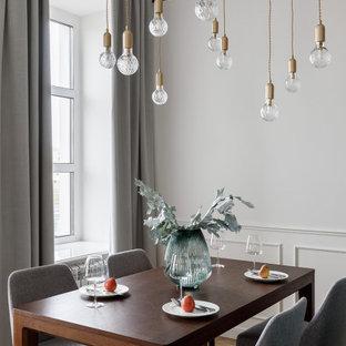 Стильный дизайн: столовая в современном стиле с белыми стенами, паркетным полом среднего тона и коричневым полом - последний тренд