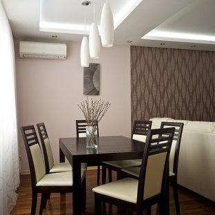 Imagen de comedor contemporáneo, pequeño, abierto, con paredes rosas, suelo de madera oscura, chimeneas suspendidas, marco de chimenea de yeso y suelo marrón