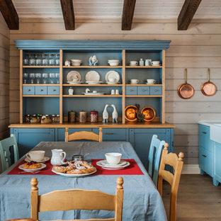 На фото: кухня-столовая среднего размера в стиле кантри с бежевыми стенами, светлым паркетным полом, бежевым полом, угловым камином, фасадом камина из камня, балками на потолке и деревянными стенами