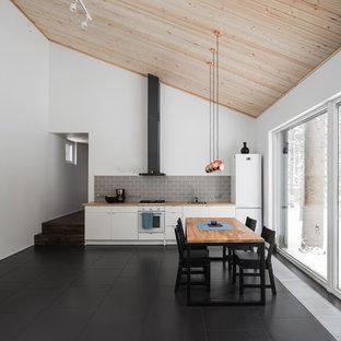 Idee per una sala da pranzo aperta verso il soggiorno design di medie dimensioni con pareti bianche, pavimento in gres porcellanato e pavimento nero