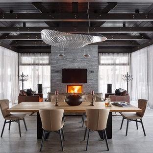 На фото: гостиная-столовая в современном стиле с стандартным камином и серым полом с