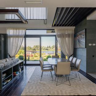 Свежая идея для дизайна: гостиная-столовая в современном стиле с серыми стенами, двусторонним камином, фасадом камина из камня и коричневым полом - отличное фото интерьера