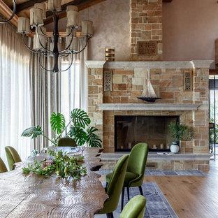 Immagine di una sala da pranzo aperta verso il soggiorno country con pareti beige, camino classico e cornice del camino piastrellata