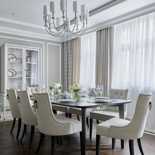 Пример оригинального дизайна: столовая в классическом стиле с серыми стенами, темным паркетным полом, многоуровневым потолком и панелями на части стены