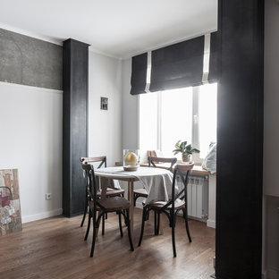 Immagine di una piccola sala da pranzo aperta verso il soggiorno minimal con pareti bianche e pavimento in legno massello medio