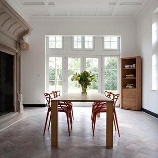 Esempio di una sala da pranzo nordica chiusa con pareti bianche, parquet chiaro e camino classico