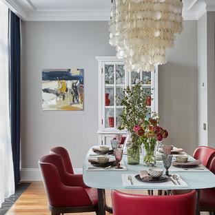 Cette image montre une salle à manger design avec un mur gris, un sol en bois brun et aucune cheminée.