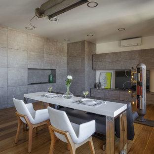 На фото: гостиная-столовая среднего размера в стиле лофт с серыми стенами, горизонтальным камином, коричневым полом и паркетным полом среднего тона с