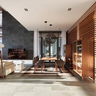 Создайте стильный интерьер: большая гостиная-столовая в современном стиле с разноцветными стенами, полом из сланца и серым полом - последний тренд