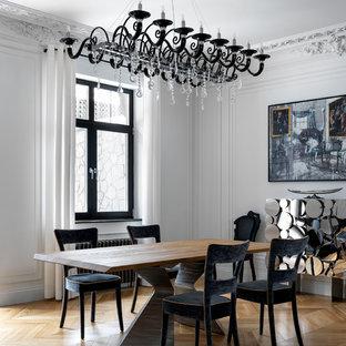 Стильный дизайн: столовая в современном стиле с белыми стенами и паркетным полом среднего тона без камина - последний тренд