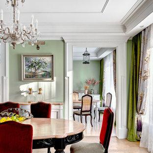 На фото: столовая в классическом стиле с зелеными стенами, светлым паркетным полом и многоуровневым потолком с
