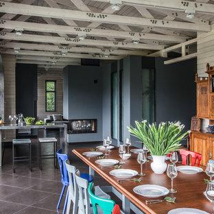Foto di una sala da pranzo aperta verso il soggiorno industriale con pareti blu, pavimento in gres porcellanato e camino bifacciale