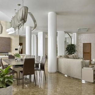 На фото: огромная гостиная-столовая в современном стиле с серебряными стенами, мраморным полом и горизонтальным камином с