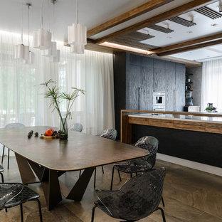 На фото: кухня-столовая в современном стиле с коричневым полом с