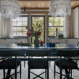 Imagen de comedor de cocina rústico, de tamaño medio, con paredes beige, suelo de baldosas de porcelana, chimenea tradicional, marco de chimenea de piedra y suelo blanco