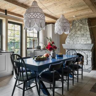 Свежая идея для дизайна: гостиная-столовая среднего размера в стиле рустика с бежевыми стенами, полом из керамогранита, стандартным камином, фасадом камина из камня и бежевым полом - отличное фото интерьера