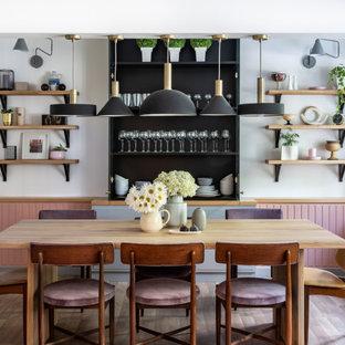 Пример оригинального дизайна: маленькая столовая в стиле ретро с белыми стенами и полом из ламината без камина