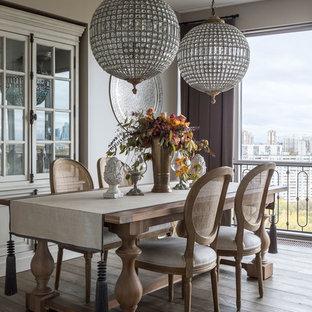 Новый формат декора квартиры: большая гостиная-столовая в классическом стиле с серыми стенами, темным паркетным полом и коричневым полом