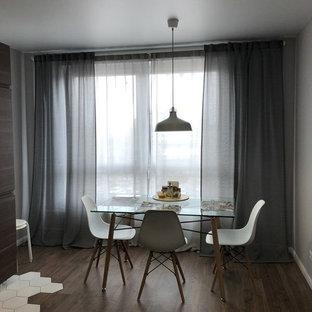 Idee per una sala da pranzo aperta verso la cucina nordica di medie dimensioni con pareti grigie, pavimento in laminato, nessun camino e pavimento marrone