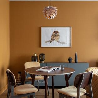 Esempio di una sala da pranzo minimal con pareti arancioni e pavimento marrone