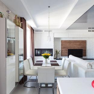Новый формат декора квартиры: гостиная-столовая в современном стиле с белыми стенами, горизонтальным камином и серым полом