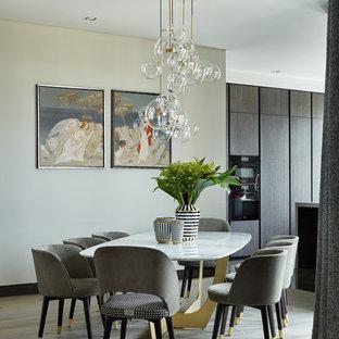 На фото: кухня-столовая в современном стиле с белыми стенами и темным паркетным полом с