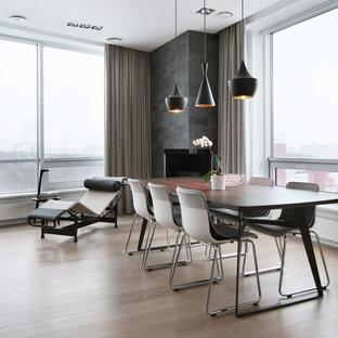 Diseño de comedor contemporáneo, abierto, con suelo de madera clara, marco de chimenea de hormigón y chimenea de esquina