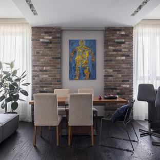 Новые идеи обустройства дома: гостиная-столовая в современном стиле с серыми стенами, темным паркетным полом и черным полом без камина