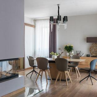Идея дизайна: гостиная-столовая в современном стиле с белыми стенами, паркетным полом среднего тона, коричневым полом, стандартным камином и фасадом камина из штукатурки