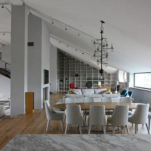 Diseño de comedor industrial, grande, abierto, con paredes grises, chimenea de doble cara, marco de chimenea de hormigón y suelo de madera en tonos medios