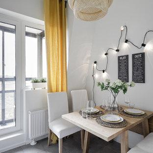 Стильный дизайн: кухня-столовая в скандинавском стиле с белыми стенами, серым полом и полом из керамогранита - последний тренд