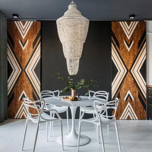 Idée de décoration pour une salle à manger ouverte sur la cuisine design avec un mur noir et un sol blanc.
