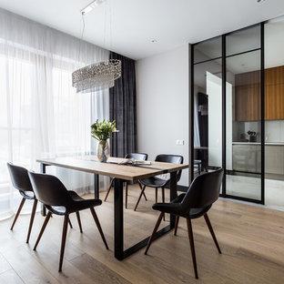 На фото: отдельная столовая в современном стиле с паркетным полом среднего тона, коричневым полом и белыми стенами с