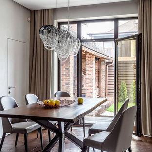 На фото: столовая в современном стиле с паркетным полом среднего тона, коричневым полом и белыми стенами с