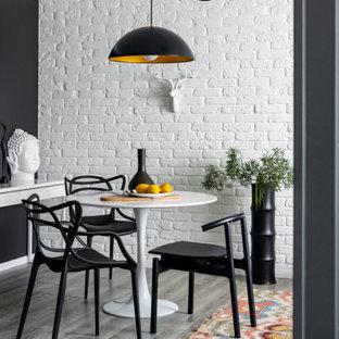 Стильный дизайн: столовая среднего размера в современном стиле с белыми стенами, серым полом и кирпичными стенами - последний тренд