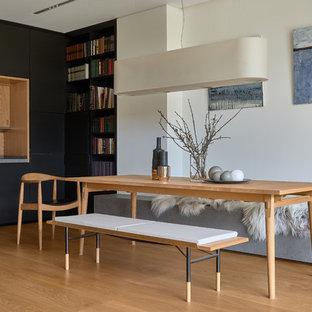 Пример оригинального дизайна: гостиная-столовая среднего размера в современном стиле с паркетным полом среднего тона, белыми стенами и коричневым полом