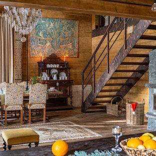 Свежая идея для дизайна: столовая в стиле рустика с коричневыми стенами, стандартным камином, фасадом камина из камня и стенами из вагонки - отличное фото интерьера