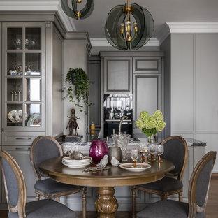 На фото: гостиная-столовая в стиле неоклассика (современная классика) с серыми стенами, паркетным полом среднего тона и коричневым полом
