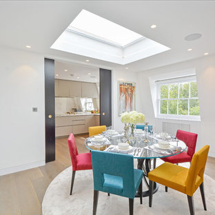 This is an example of a small contemporary dining room in London with white walls, light hardwood flooring and beige floors.