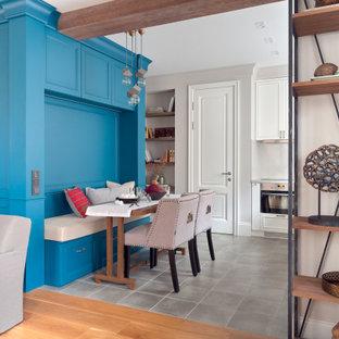 На фото: столовая в стиле современная классика с с кухонным уголком, синими стенами и серым полом с